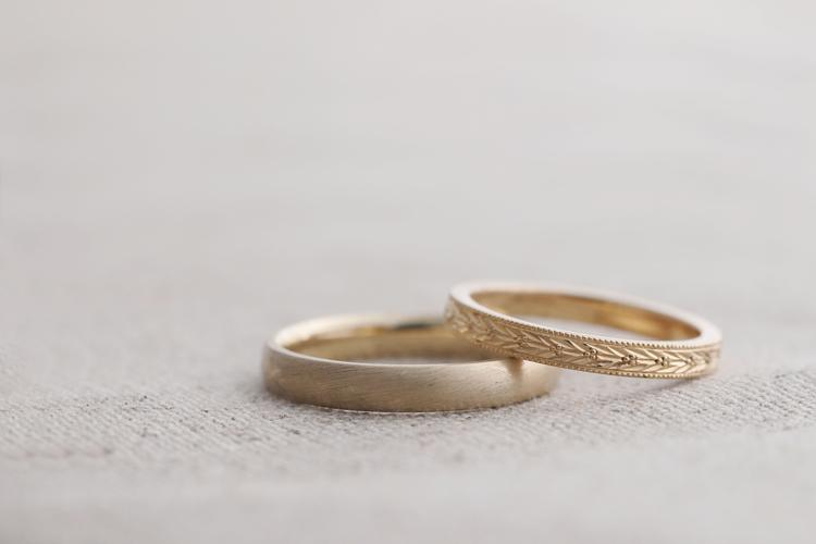 マットな仕上げの指輪と手彫り加工を施したゴールドの指輪